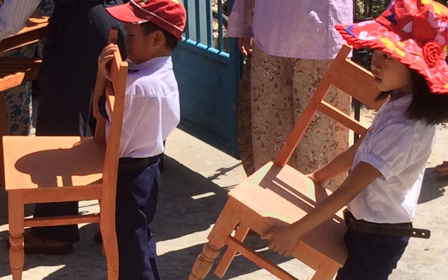 Students carrying chairs